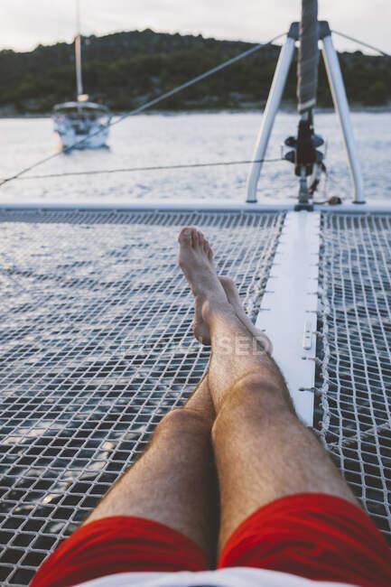 Человек лежит в лодке, плывущей по озеру — стоковое фото
