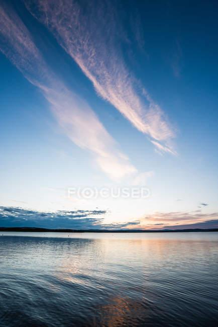 Superficie de tranquilo lago azul con cielo dramático al atardecer - foto de stock