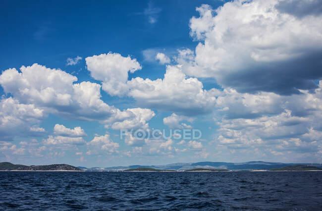 Блакитне хвилясте море з горами під небом покриті білими хмарами. — стокове фото