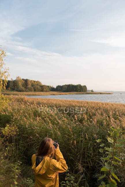 Back view of woman standing in high grass on shore of lake and taking photo of landscape in autumnal sunlight — Stock Photo