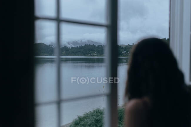 Woman looking through window of room — Stock Photo