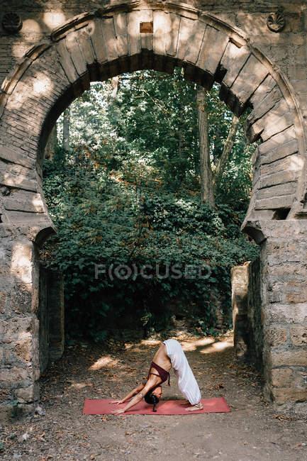 Mujer de pie en Downward-Facing Dog pose mientras hace yoga bajo el viejo arco desmoronado - foto de stock