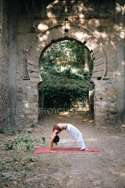 Femme se pencher en arrière tout en faisant du yoga sous la vieille arche qui s'effrite — Photo de stock