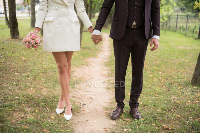 Faceless shot of elegant trendy couple holding hands and standing on pathway in green park — Stock Photo