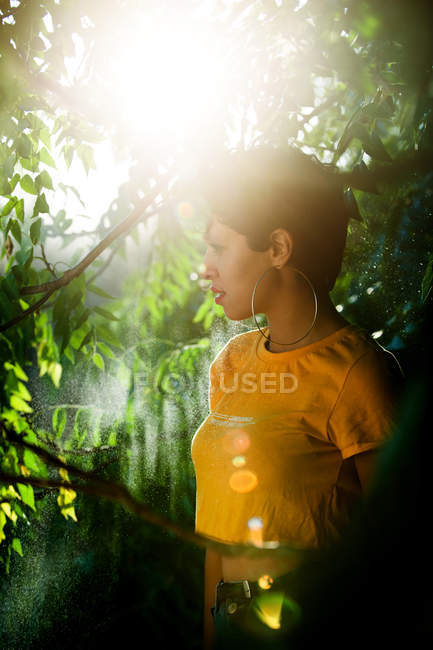 Thoughtful sensual brunette with short hair standing in mist in green vegetation with sunlight — Stock Photo