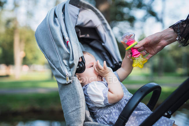 Close-up of female hand comforting baby in carriage outdoors — Stock Photo