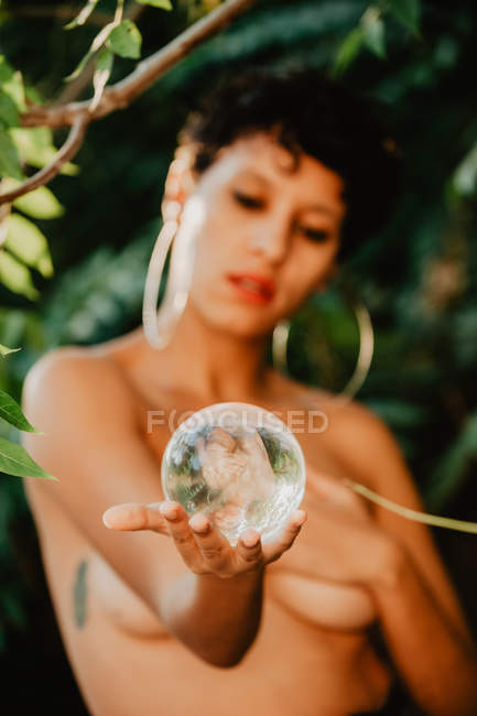 Young topless brunette woman covering breast and holding glass transparent ball in green woods — Stock Photo