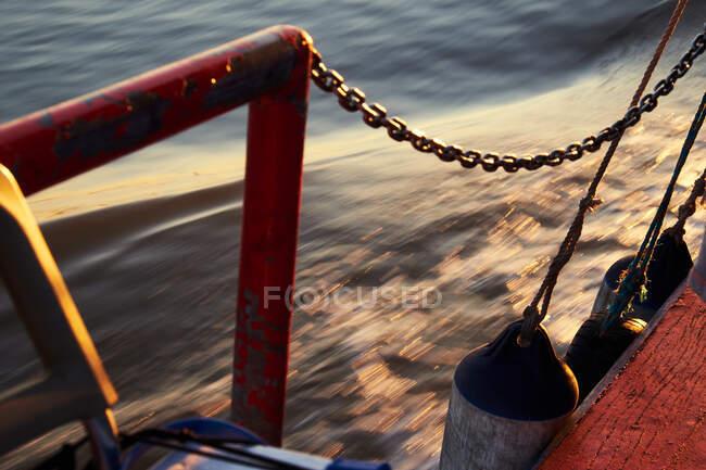 Длительное фото отражающих водяных завихрений с видом с лодки с красным стальным забором и цепями — стоковое фото