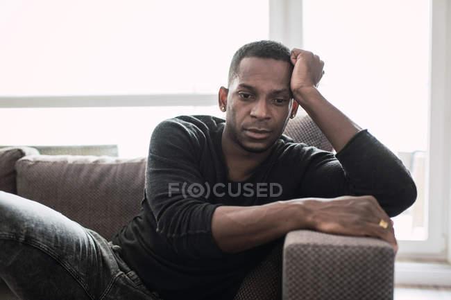 Sognando adulto nero uomo appoggiato sulle mani mentre seduto sul divano e guardando lontano in finestra lucida — Foto stock