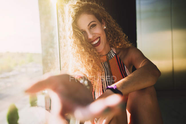 Young curly woman sitting in bright sunshine and outstretching blurred hands with smile — Stock Photo