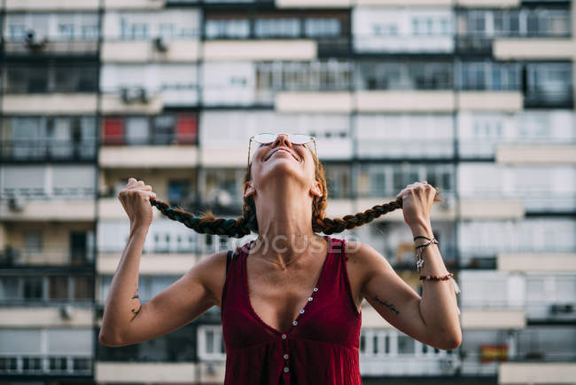Cheerful red-haired young woman in sunglasses holding braids against residential building — Stock Photo
