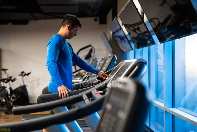 Young man in blue sport pullover doing exercise on treadmill in gym — Stock Photo