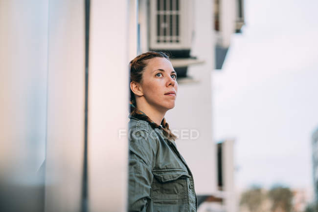 Thoughtful red-haired girl with braids leaning on wall in city — Stock Photo