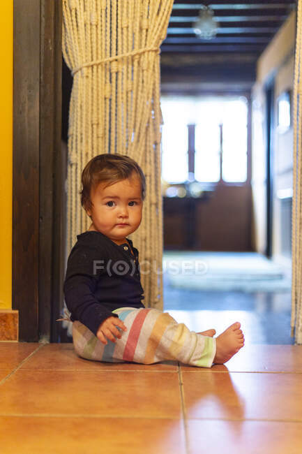 Вид сбоку восхитительного младенца, сидящего в одиночестве на кафельном полу в холле, глядя в камеру — стоковое фото
