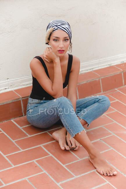 Giovane donna seduta al piano vicino al muro — Foto stock