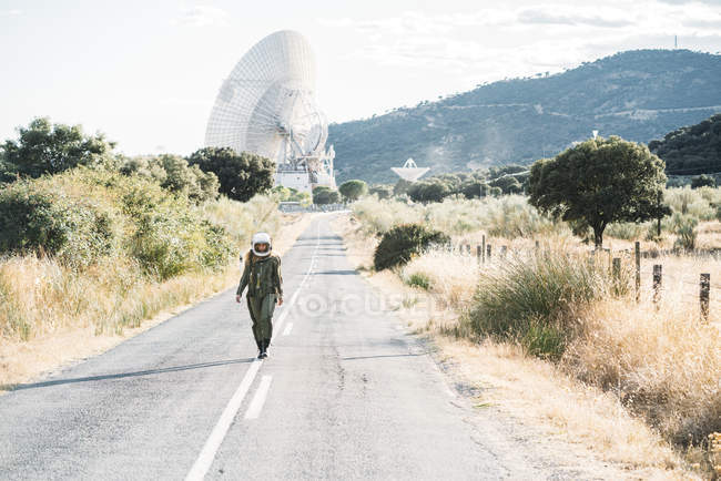 Woman in astronaut costume and helmet walking along road in countryside — Stock Photo