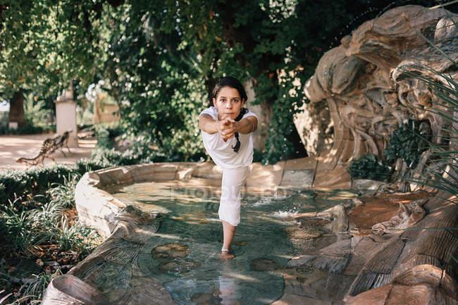 Mulher de pé na água da fonte em pose de árvore ao fazer ioga no parque — Fotografia de Stock
