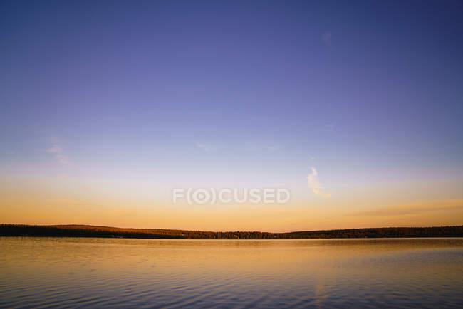 Paesaggio di lago calmo con alberi in orizzonte sotto cielo limpido e nuvoloso al tramonto — Foto stock