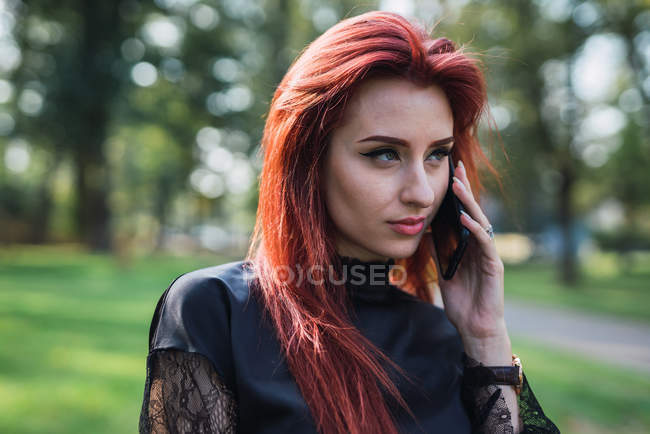 Young woman with ginger hair talking on smartphone in sunny park — Stock Photo