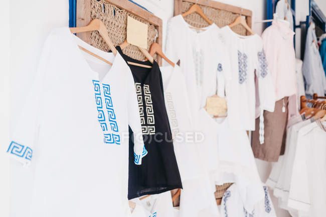 White and black cotton clothes on hangers at street market Mykonos, Greece — Stock Photo