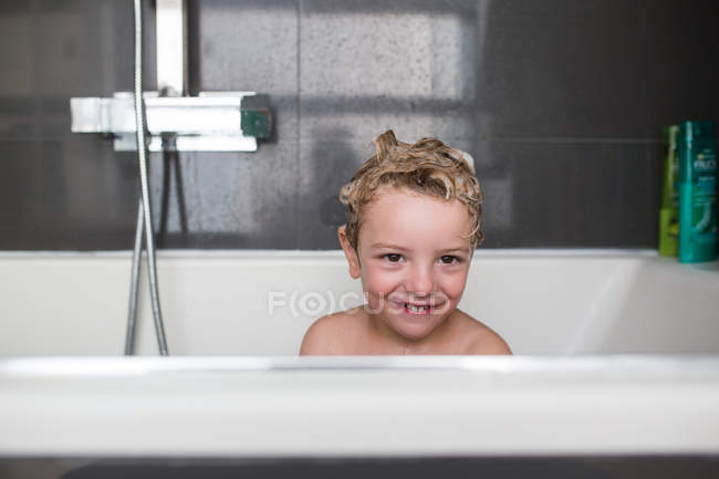 Portrait of smiling little boy sitting in bath — Stock Photo