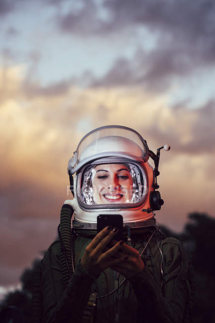Smiling female astronaut using mobile phone against sunset sky — Stock Photo