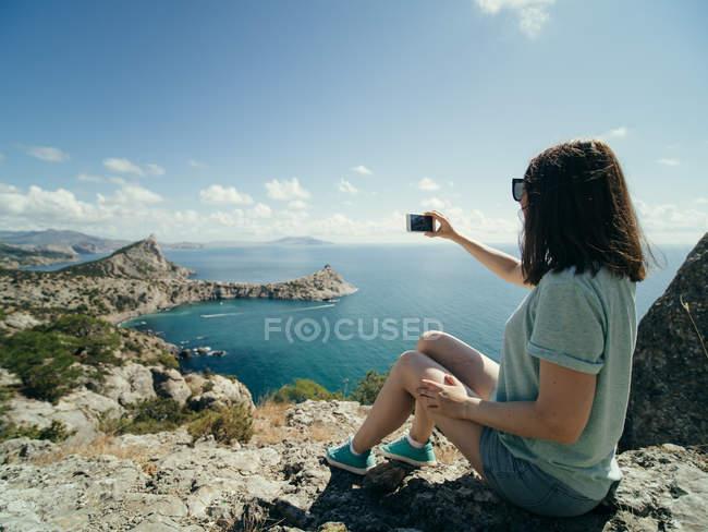 Женщина делает селфи с мобильного телефона на скале с морской накидкой на заднем плане — стоковое фото