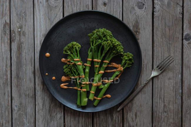 Gedämpfter Brokkoli mit Rommesco-Sauce auf schwarzem Teller mit Gabel auf Holztisch — Stockfoto