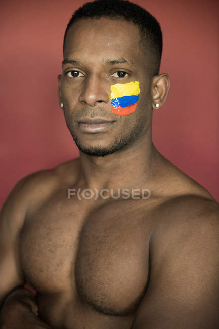 Portrait of African American man with colombian flag on face looking at camera — Stock Photo