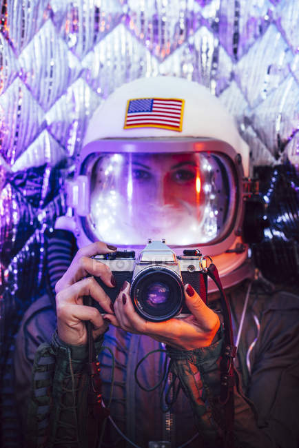 Girl wearing old space helmet and costume holding photo camera — Stock Photo
