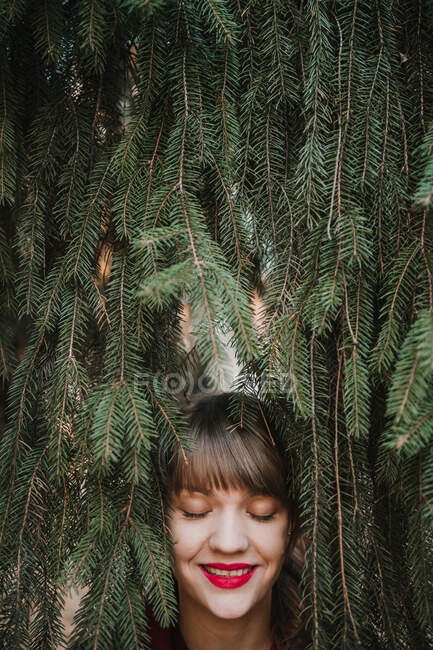 View of crop young lady's face holding coniferous branch and looking away — Stock Photo