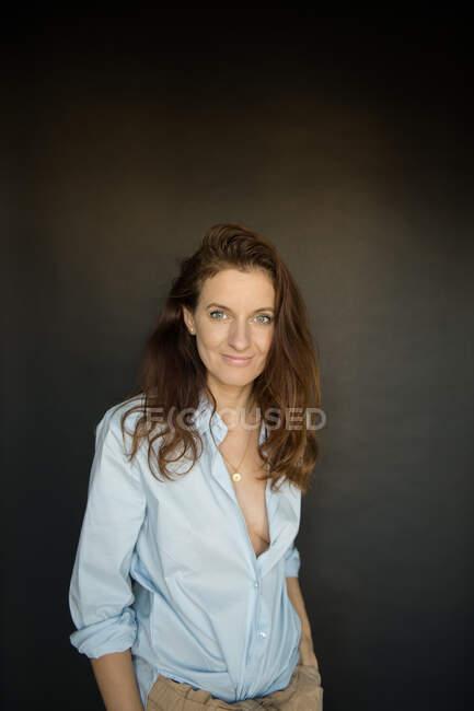 Mulher adulta atraente em blusa elegante sorrindo e olhando para a câmera enquanto estava em pé sobre fundo preto — Fotografia de Stock