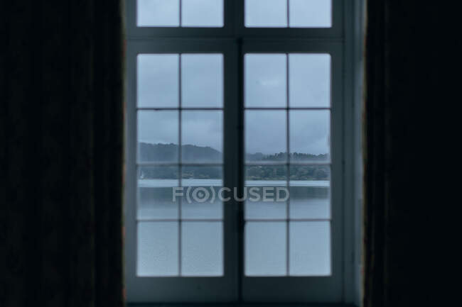 Озеро и гора через окно — стоковое фото