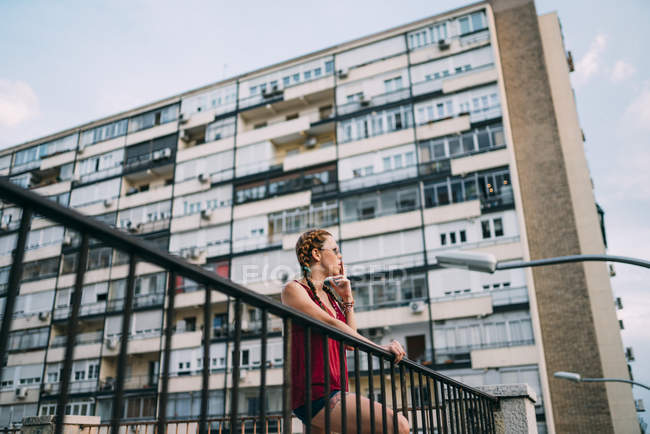 Red-haired young woman with braids and sunglasses standing against residential building — Stock Photo