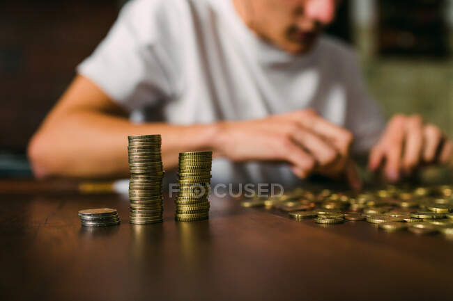 Anonymous young man counting shiny coins and stacking them on wooden table — Stock Photo