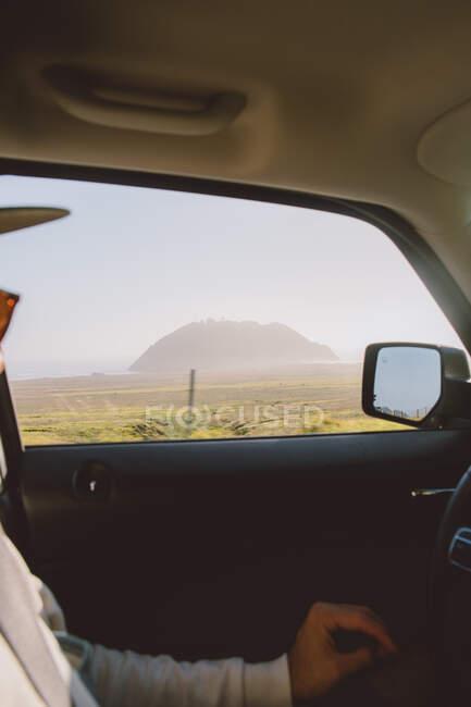 Неузнаваемый парень за рулем современного автомобиля в удивительной сельской местности в большом сюре, Калифорния — стоковое фото