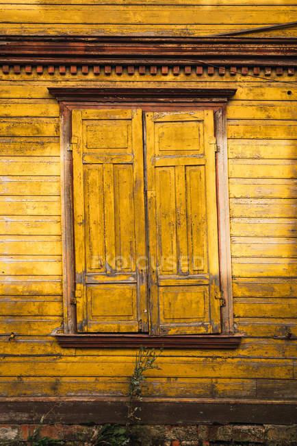 Finestra con persiane chiuse situata sulla parete in legno della casa di campagna gialla — Foto stock