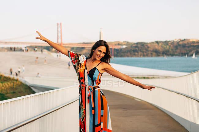 Элегантная женщина в платье стоя на мосту с распростертыми объятиями и просматривает камеры — стоковое фото