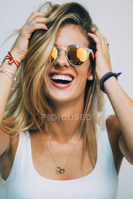 Молода блондинка жінка в Білий топ і сонцезахисні окуляри, стоячи і зворушливо волосся на білому тлі — стокове фото