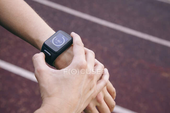 Crop shot of female hands wearing smart watch and using device on racetrack — Stock Photo