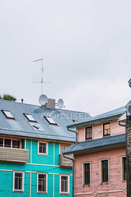 Two buildings with satellite dishes on roof in small town against cloudy sky — Stock Photo