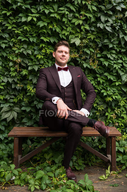 Excited man wearing trendy wedding suit and looking at camera — Stock Photo