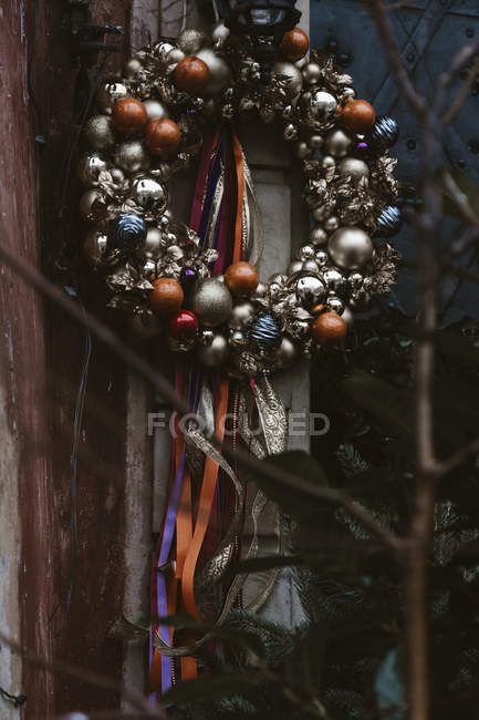 Christmas wreath decorated with gold and red balls, hanging on outside of house — Stock Photo
