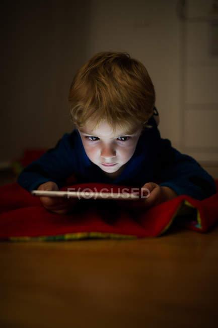 Petit garçon regarder des dessins animés avec tablette numérique sur le sol en bois — Photo de stock