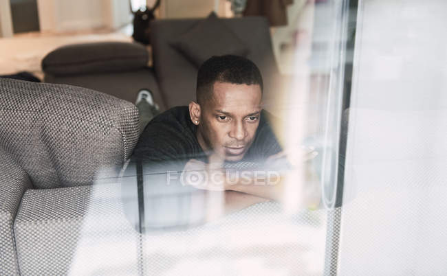 Dreaming black man leaning on hands while sitting on couch and looking away — Stock Photo