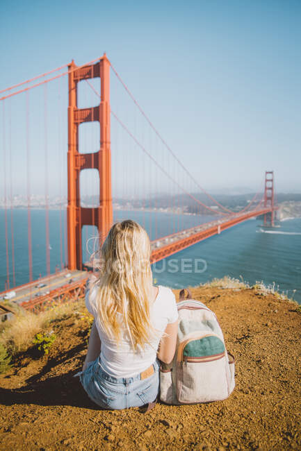 Back view of young female sitting on ground near backpack and looking at famous Golden Gate Bridge in San Francisco, California — стокове фото