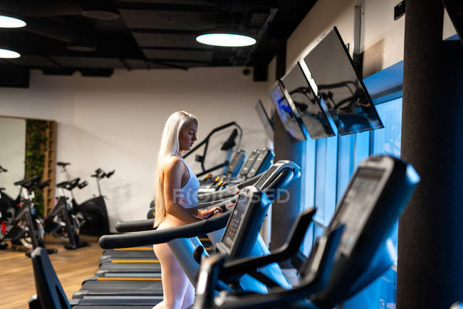 Athletic blond woman jogging on treadmill in gym — Stock Photo
