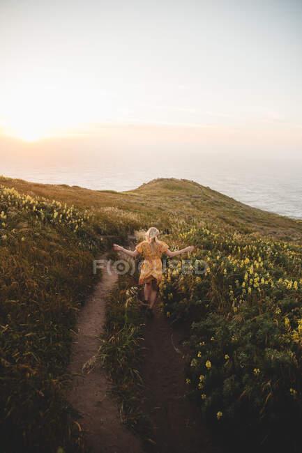 Вид сзади молодой женщины в симпатичном платье, бегущей по сельской тропе к спокойному морю во время великолепного восхода солнца в точке Рейес, ca — стоковое фото