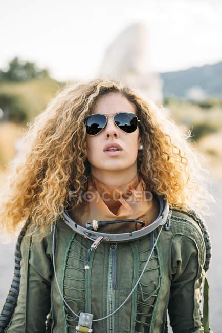 Retrato de astronauta fêmea em traje espacial em pé ao ar livre — Fotografia de Stock