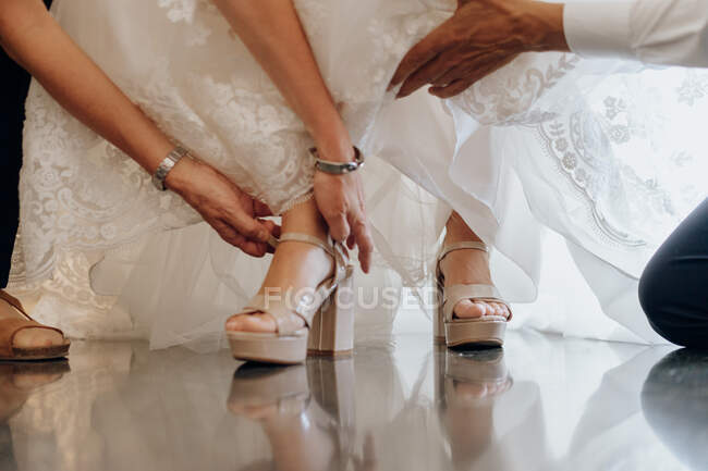 Crop man helping bride with high heels — Stock Photo